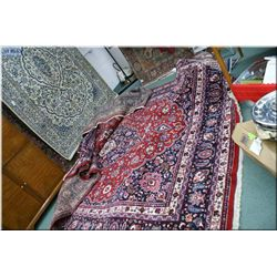 A large Iranian wool area rug with center medallion, multiple wide border, floral motif in shades of