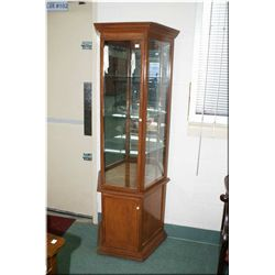 A single door display cabinet with three glass shelves, mirrored back and under storage
