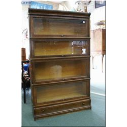 An oak four tier Barrister's book case with single drawer base
