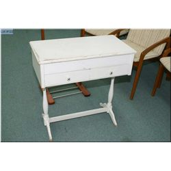 A white child sized vanity with two drawers and flip-top.
