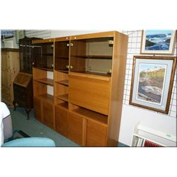 A three piece teak shelving unit with smoked doors and drop front liquor storage