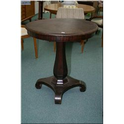 A single pedestal Victorian style leather topped table