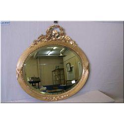 A vintage oak leaf motif framed wall mirror