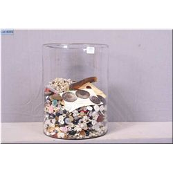 A large glass cylinder filled with vintage buttons and beads etc.