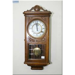 A vintage hanging wall clock with enamel face and visible pendulum