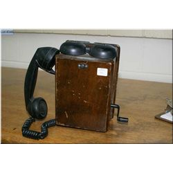 A vintage wooden wall phone with handset