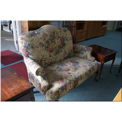 A small tapestry upholstered loveseat with carved ball claw feet