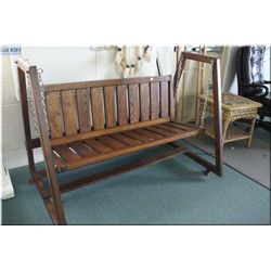 A wooden swinging garden bench with frame