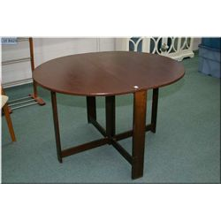 A wooden drop leaf table with gate leg supports