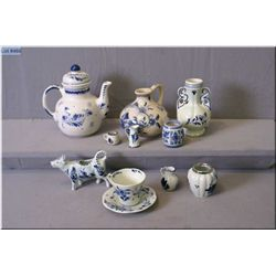 A selection of Delft pottery including tea pot, double handled vase, cow creamer, small handled jug