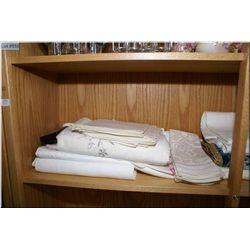 A selection of vintage linens including table clothes, napkins, doilies etc.
