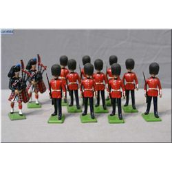 A selection of metal figures including Britians Scots guards, pipers, guards etc. 12 figures total