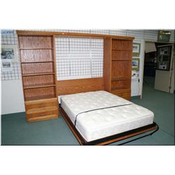 A folding double door Murphy bed with pillow top mattress and two matching bookcase sides with under