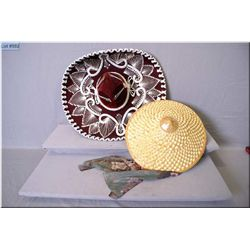 A Mexican sombrero and a Chinese sun hat and a large spoon and fork for the wall