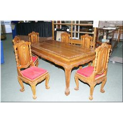 A teak dining table and six upholstered teak chairs with heavily carved Oriental decoration and upho
