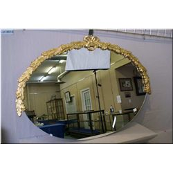 A vintage oval mirror with bow and floral garland frame