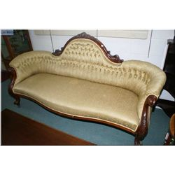 A Victorian gold upholstered and button tufted curved back sofa with carved back and supports