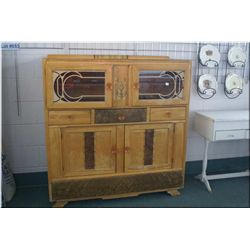 A deco style cabinet with double glazed doors, three drawers and under storage