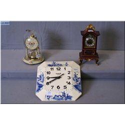 Three clocks including a German anniversary clock, a miniature grandfather alarm clock, and a Delft