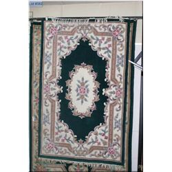 100% wool area rug with large floral center medallion and border in shades of emerald green and past