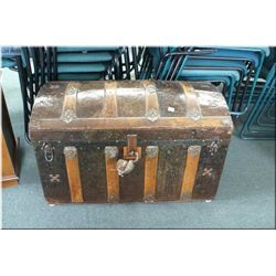 A vintage metal dome topped trunk with wooden bindings
