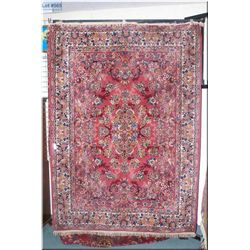 A large wool area rug with center medallion and triple border in shades of salmon, cream and gold 77