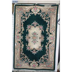 A wool area rug with large floral center medallion and border in shades of emerald green and pastels