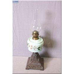 Antique oil lamp with cast iron base and hand enamelled glass bowl