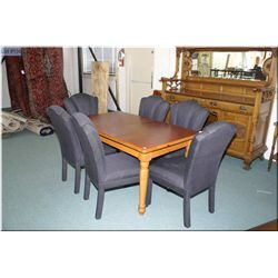A knotty pine dining table with two leaves and six black upholstered dining chairs