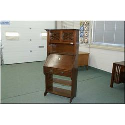 Quarter cut oak antique Mission style drop front desk with lower book storage and two door galley