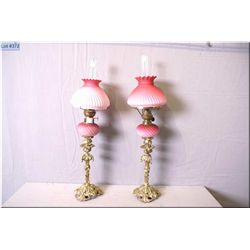 A pair of matching oil lamp on cast brass pedestals with pink satin glass globes and shades