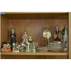 A shelf lot of collectibles including an Anniversary style figural lamps, hurricane candle holders,