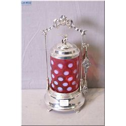 A cranberry and milk glass polka dot pickle castor in silver plate galley with tongs and bird finial