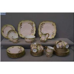 An antique French porcelain tea set with hand enamelling and gilt decoration including cream and sug