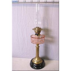Antique oil lamp on column style pedestal and pink glass bowl with double burner