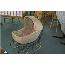 An antique woven wicker doll buggy