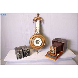 Three vintage box cameras including two Brownie Targets, and a vintage wooden wall mount barometer