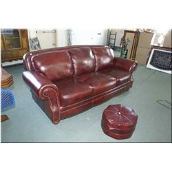 A full sized burgundy leather upholstery sofa and ottoman