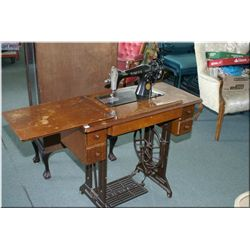 Singer treadle sewing machine in walnut and cast cabinet