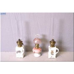Three small vintage oil lamps including a matched pair of National Theatre Muchin porcelain lamps wi