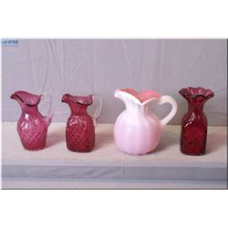 Two Cranberry Chalet glass jugs with clear handles, cranberry glass quilted vase and a pink cased gl