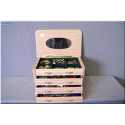 A wooden jewellery box filled with vintage and collectible costume jewellery including rhinestone br