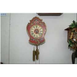 A wooden two train, chiming wall clock with decorative floral face