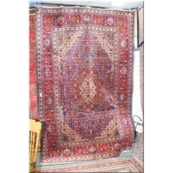 Iranian wool area rug with center medallion, multiple borders, floral design in shades of red, blue,