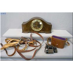 A cased pair of binoculars, a Emes mantle clock and a horse bridle