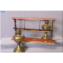 A counter top craft paper dispenser and two brass oil lamps