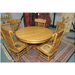 A modern oak center pedestal table with carved claw feet and five pressed back chairs