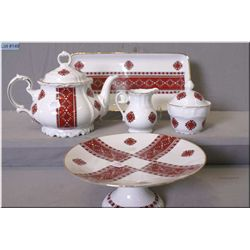 A collection of Bavarian Ukrainian red and white serving pieces including cake comport, teapot, lidd