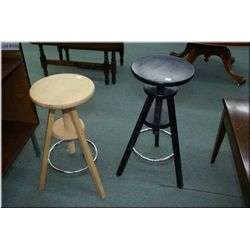 A pair of modern adjustable stools, one in natural finish, one black