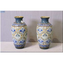 A pair of Doulton Lambeth glazed stoneware vases with raised floral pattern on mottled beige backgro